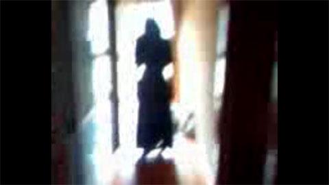 携帯に映り込んだ黒いワンピースの女性